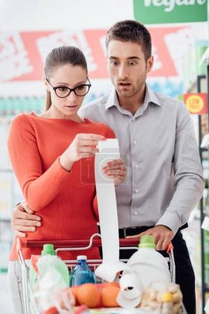 Young couple shopping at the supermarket, they are pushing a cart and checking a long receipt, lifestyle and budgeting concept