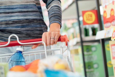 Woman doing grocery shopping at the supermarket and pushing a full shopping cart, hand detail close up, lifestyle concept