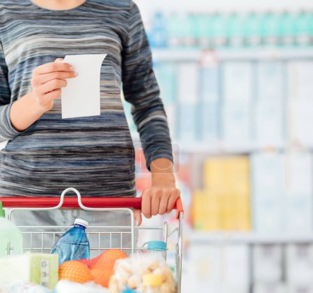 Young woman shopping at the supermarket, she is pushing a cart and reading a grocery list