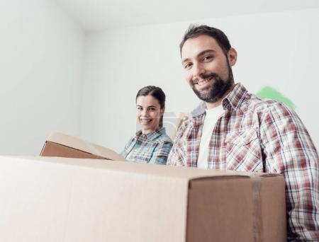 Young smiling couple moving into a new house, they are carrying full cardboard boxes