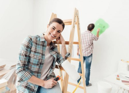 Home makeover and renovation: young couple painting their new house, the man is using a paint roller and the woman is leaning on a ladder and smiling