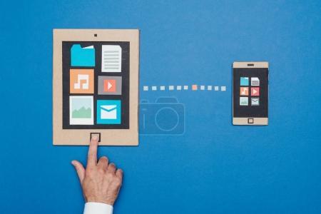 Photo pour Appareils mobiles connectés : synchronisation des données et transfert de fichiers, smartphone créatif et tablette en carton recyclé - image libre de droit