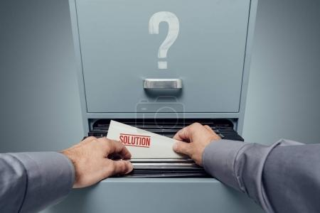 Office clerk searching for files in the filing cabinet, he finds a folder with business solutions inside, personal point of view