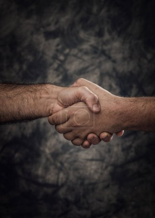 Photo pour Hommes donnant une poignée de main sur la notion de contexte, de partenariat et de coopération grunge noir - image libre de droit