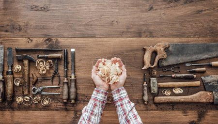 Professional carpenter holding wood shavings and vintage woodworking tools on a workbench, top view