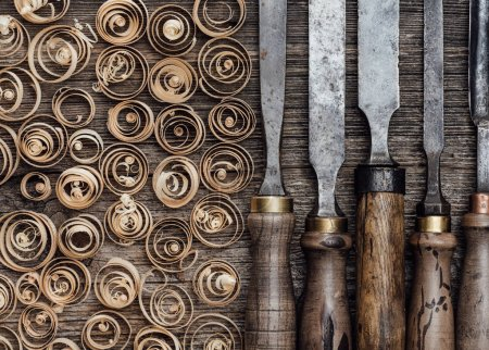Set of used professional carving tools on the workbench and wood shavings close up: carpentry, craftsmanship and handwork concept
