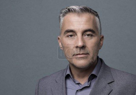 Foto de Hombre de negocios maduro confianza posando sobre fondo gris, él está mirando a cámara - Imagen libre de derechos