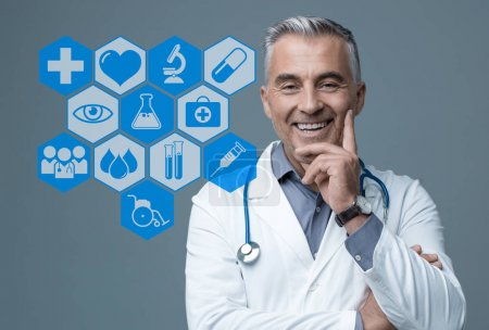 Confident mature doctor smiling at camera and interactive medical icons interface
