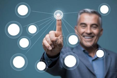 Smiling businessman using a virtual interface, he is pointing with a finger