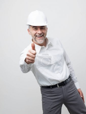 Cheerful happy professional engineer and architect wearing a safety helmet and giving a thumbs up