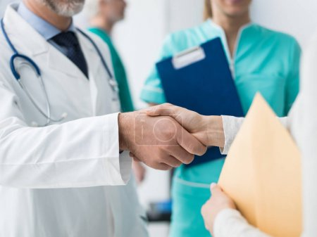 Doctor and patient shaking hands after a consultation at the hospital and medical team, medical exams and healthcare concept