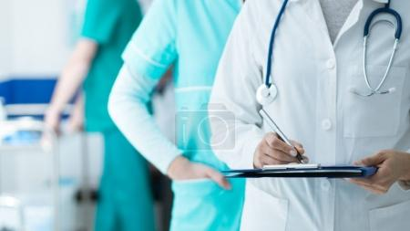 Medical staff working at the hospital: doctor and nurse checking a patient's medical record on a clipboard, healthcare and medical exams concept