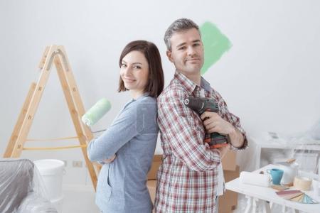 Foto de Sonriendo pareja amorosa haciendo renovaciones en casa, la mujer está sosteniendo un rodillo de pintura y el hombre está utilizando un taladro - Imagen libre de derechos