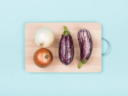 Photo for Onions and eggplants on a wooden chopping board, food preparation and healthy eating concept - Royalty Free Image