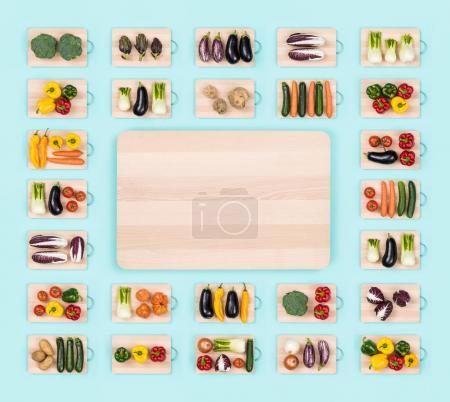 Photo for Fresh raw healthy vegetables on wooden chopping boards frame and copy space at center, healthy eating concept - Royalty Free Image