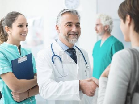 Smiling doctor shaking patients hand