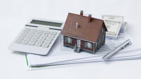 Photo pour Maison modèle, calculatrice, argent comptant et paperasserie sur un bureau : concept immobilier, prêt immobilier et investissement - image libre de droit