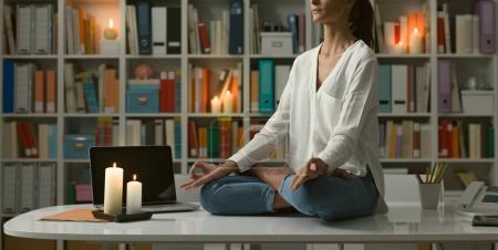 Photo pour Détente femme pratiquant la méditation à la maison pendant la nuit, elle est assise dans la position du lotus sur le Bureau - image libre de droit