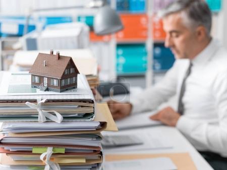 Photo pour Agent immobilier travaillant dans le bureau et le tas de paperasse, maison modèle sur la documentation de prêt de premier plan et d'hypothèque - image libre de droit
