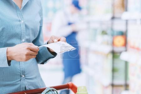 Foto de Mujer haciendo compras ir de compras en el supermercado, empujando un carrito y comprobación de elementos de una lista - Imagen libre de derechos