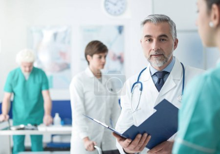 Photo for Professional doctor and medical staff working at the hospital, he is examining patient's medical records - Royalty Free Image