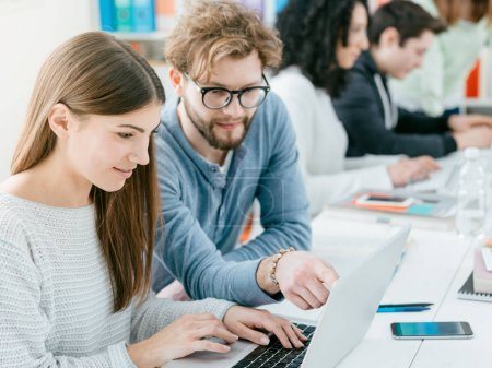 Photo for Young smiling university students at the library: they are studying together, connecting online and pointing at the laptop's screen - Royalty Free Image