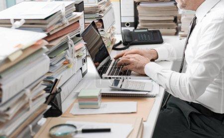 Photo pour Homme d'affaires travaillant dans le bureau et piles de documents, il se connecte avec un ordinateur portable et dactylographier - image libre de droit