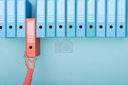 Photo pour Office worker prenant un dossier en surbrillance dans l'archive : base de données, concept d'administration et de gestion de fichiers - image libre de droit