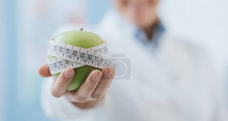 Photo for Professional nutritionist holding a fresh apple with tape measure: diet and weight loss concept - Royalty Free Image