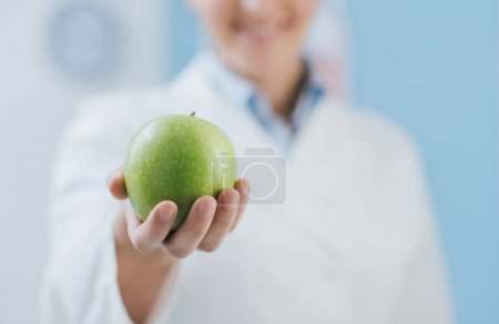 Photo for Professional nutritionist holding a fresh apple and smiling: nutrition and diet concept - Royalty Free Image