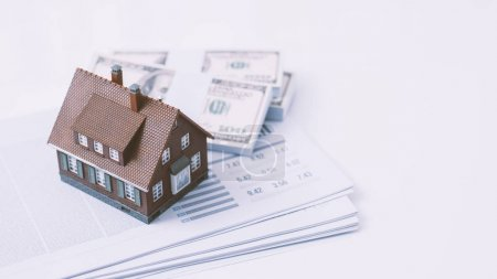 Photo for Model house, paperwork and cash money on a desktop: real estate, home loan and investments concept - Royalty Free Image