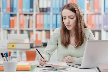 Photo pour Jeune étudiante à l'université assise au bureau, se connectant à un ordinateur portable et étudiant un livre - image libre de droit