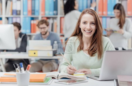 Photo for Young smiling female university student sitting at desk and studying a book, group of students on the background, learning and education concept - Royalty Free Image