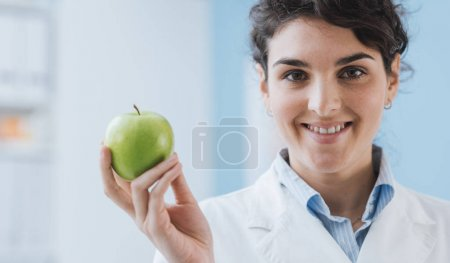 Professional nutritionist holding a fresh apple and smiling: nutrition and diet concept