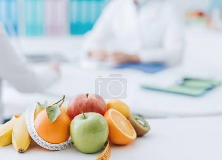 Professional nutritionist meeting a patient in the office and healthy fruits with tape measure on the foreground: healthy eating and diet concept