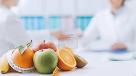 Photo pour Nutritionniste professionnel rencontrant un patient au bureau et fruits sains avec ruban à mesurer au premier plan : saine alimentation et concept de régime alimentaire - image libre de droit