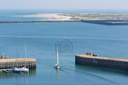 Photo pour Voilier quittant le port de Helgoland, île allemande dans la mer. À l'horizon de la plus petite Dune île. - image libre de droit