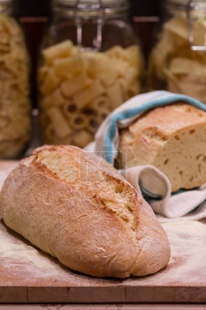 Bread laid on a chopping board, with pasta bowls in the backgrou