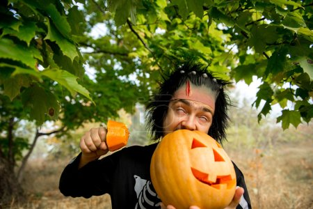 Terrible man. Human zombies holding a pumpkin in her hands. Symbol of the holiday Halloween.
