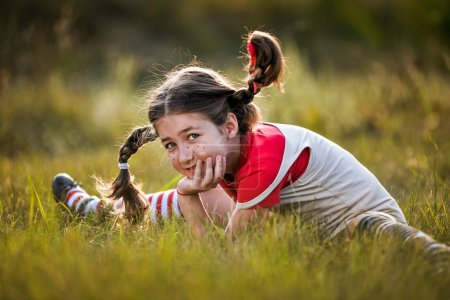 girl with pigtails imagines the summer on the nature