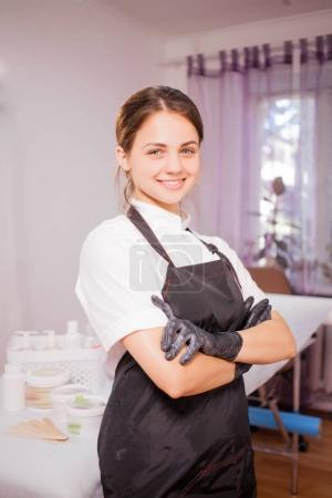 Young girl beautician stands with hands clasped and smiling
