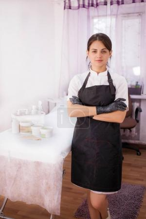 A beautician girl stands in a black apron and gloves