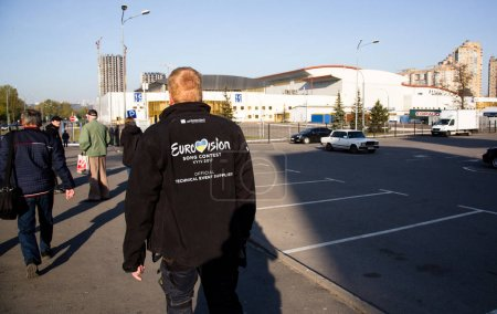 Photo for KYIV, UKRAINE - APRIL 21, 2017: Worker of Eurovision song contest walks near International Exhibition Centre in Kyiv, Ukraine - Royalty Free Image