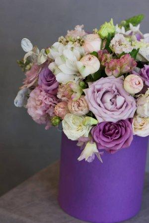 der schöne Blumenstrauß in lila Schachtel auf grauem Hintergrund