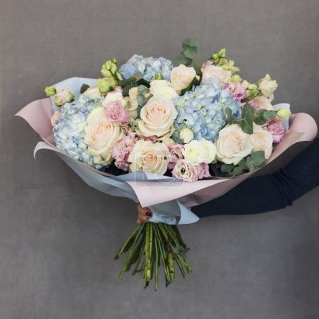 der elegante Strauß aus Rosen und Hortensien in Frauenhänden