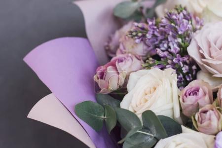 Flieder und Eukalyptus in einem großen zarten Bouquet auf grauem Hintergrund
