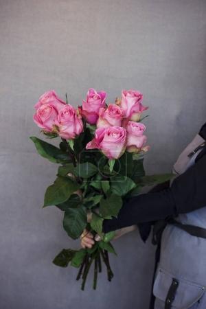 junge Floristin mit einem großen Strauß rosa Rosen