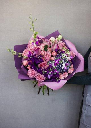 das schöne rustikale Bouquet in violetten Tönen in Frauenhänden