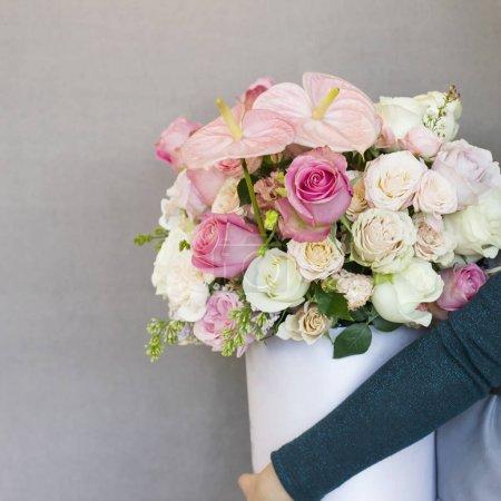 der schöne Strauß verschiedener Rosen in weißer Schachtel in Frauenhänden