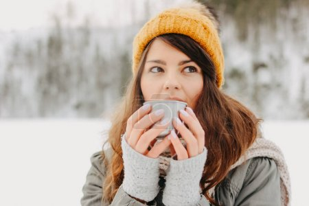 Brunette girl in yellow knitted hat with metal mug of hot tea in forest outdoors in winter